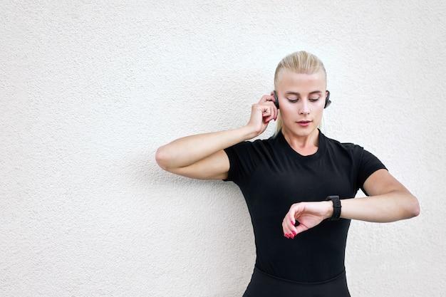 Porträt der jungen sportlichen frau, die schwarze sportkleidung und modische weiße turnschuhe trägt