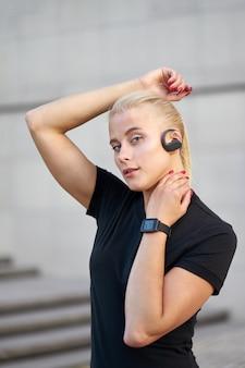 Porträt der jungen sportlichen frau, die schwarzes hemd trägt und hören musik. außenaufnahme auf grauem wandhintergrund.