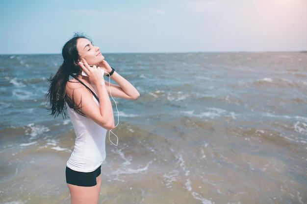 Porträt der jungen sportlichen frau in den entspannenden kopfhörern beim sitzen nahe ozean im sommer, attraktive hörende lieblingsmusik der frau während der erholungszeit am wochenende.
