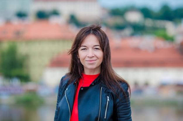 Porträt der jungen städtischen frau in der europäischen stadt auf der berühmten brücke. früher morgen des warmen sommers in prag, tschechische republik