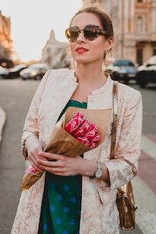 Porträt der jungen stilvollen attraktiven frau, die in der stadt geht