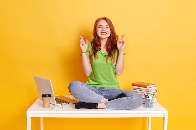 Porträt der jungen studentin, die auf ihrem schreibtisch sitzt und ihre finger kreuzt, wünscht, für zukünftige projekte glücklich zu sein, hat aufgeregten ausdruck, schließt augen, trägt lässig, isoliert über gelber wand.