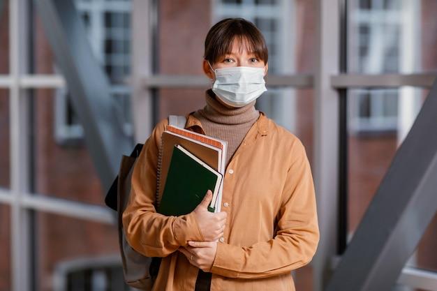 Porträt der jungen studentin, die eine medizinische maske trägt