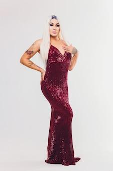 Porträt der jungen transgenderfrau auf rotem kleid mit pailletten