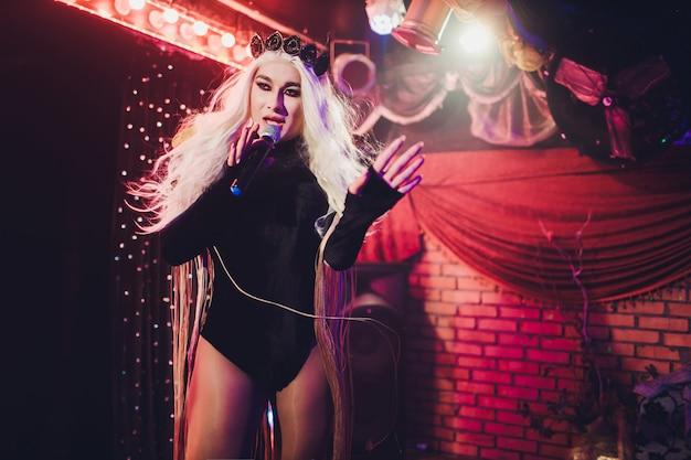 Porträt der jungen transgenderfrau im hellen kostüm auf farbigem hintergrund.