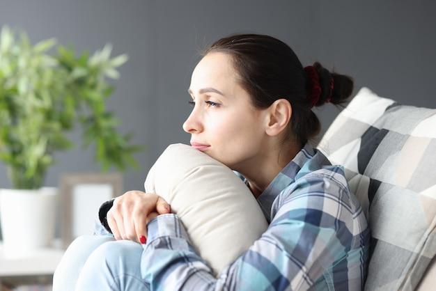 Porträt der jungen traurigen frau, die auf couch sitzt