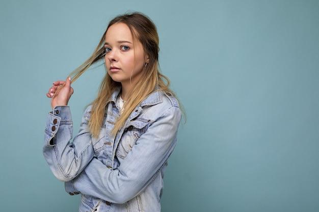 Porträt der jungen traurigen verärgerten attraktiven blonden frau mit aufrichtigen gefühlen, die hipster-denim trägt