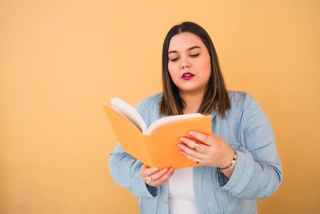Porträt der jungen übergrößenfrau, die freizeit genießt und ein buch liest, während sie gegen gelben raum steht. lifestyle-konzept.