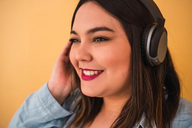 Porträt der jungen übergrößenfrau, die musik mit kopfhörern draußen gegen gelben raum hört.