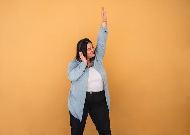Porträt der jungen übergrößenfrau, die musik mit kopfhörern im freien gegen gelb hört.