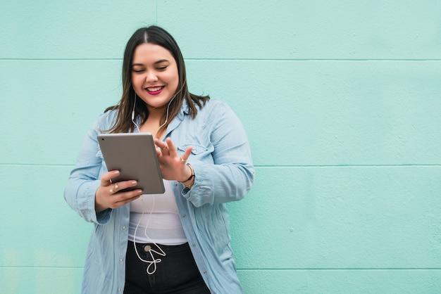 Porträt der jungen übergrößenfrau, die musik mit kopfhörern und digitalem tablett im freien hört.