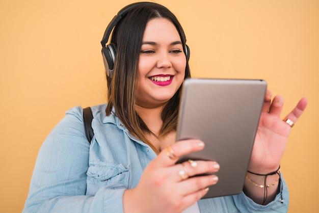 Porträt der jungen übergrößenfrau, die musik mit kopfhörern und digitalem tablett im freien hört