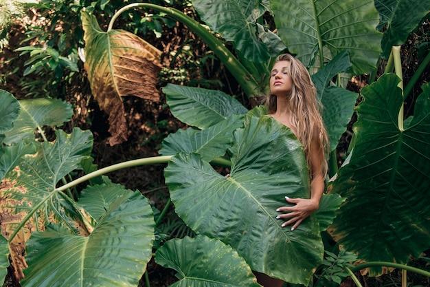 Porträt der jungen und schönen frau mit perfekter glatter haut und dem langen haar in den tropischen blättern. von naturkosmetik und hautpflege. -