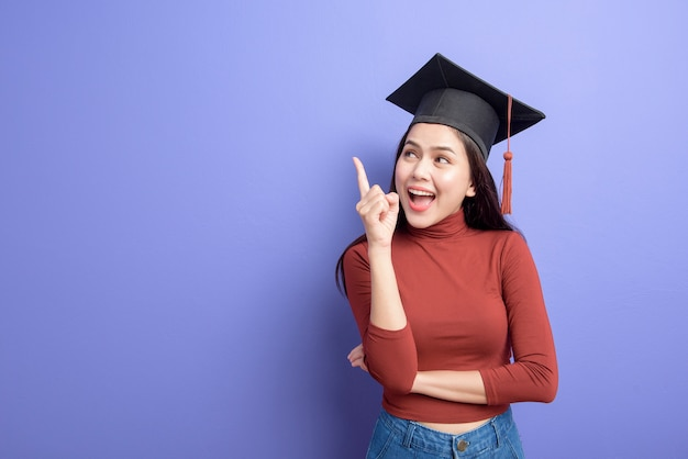 Porträt der jungen universitätsstudentenfrau mit abschlusskappe auf veilchen