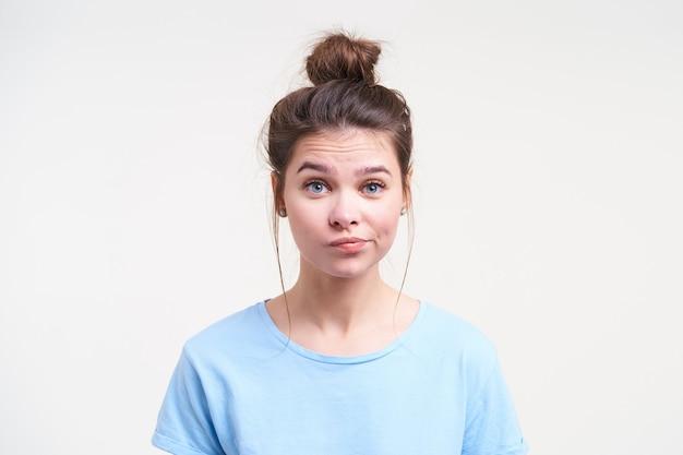 Porträt der jungen verwirrten braunhaarigen dame mit brötchenfrisur, die ihren mund verdreht, während sie ratlos nach vorne schaut und über weißer wand steht