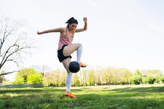 Porträt der jungen weiblichen fußballspielerin, die fähigkeiten auf dem fußballplatz trainiert und übt. sportkonzept.