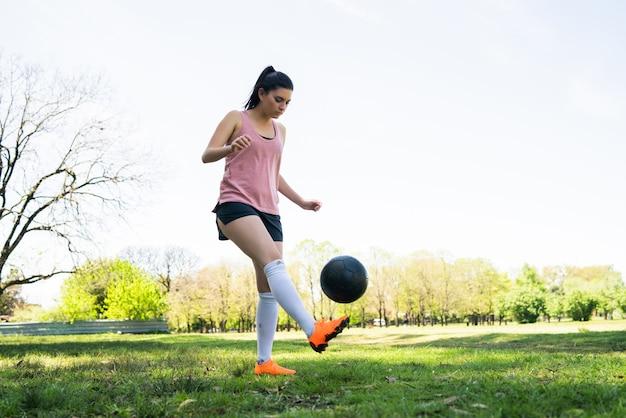 Porträt der jungen weiblichen fußballspielerin, die fähigkeiten auf dem fußballplatz trainiert und übt