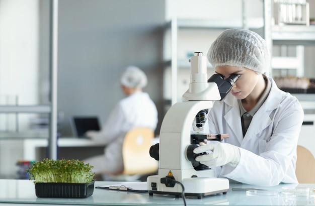 Porträt der jungen wissenschaftlerin, die im mikroskop schaut, während pflanzenproben im biotechnologielabor, kopierraum studieren