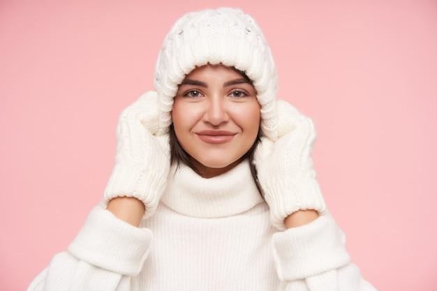 Porträt der jungen ziemlich positiven grünäugigen frau, die an ihrer weißen strickmütze zieht, während sie mit angenehmem lächeln nach vorne schaut und über rosa wand aufwirft