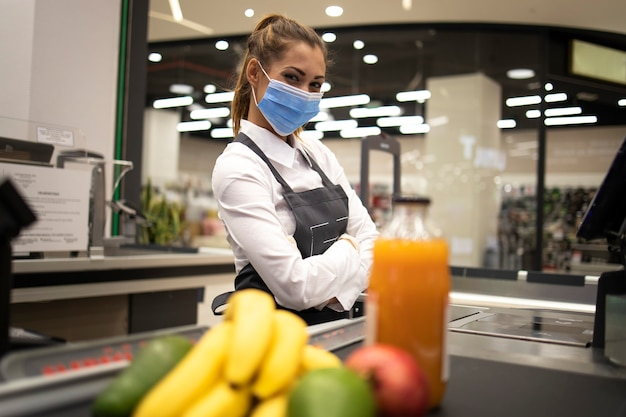 Porträt der kassiererin im supermarkt mit maske und handschuhen, die vollständig gegen das koronavirus geschützt sind