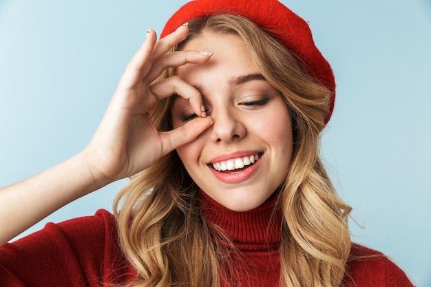 Porträt der kaukasischen blonden frau 20s, die rote baskenmütze trägt, die ok zeichen im stehen zeigt, lokalisiert