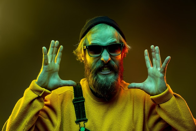 Porträt der kaukasischen frau auf gradientenraum im neonlicht. schönes männliches modell mit hipster-stil in gläsern Kostenlose Fotos