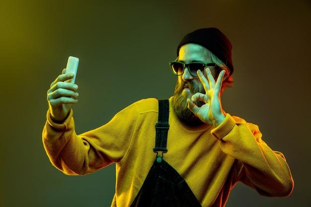 Porträt der kaukasischen frau auf gradientenraum im neonlicht. schönes männliches modell mit hipster-stil in gläsern