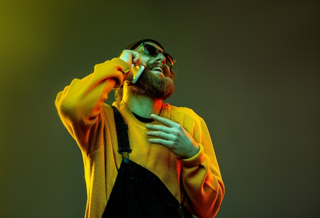 Porträt der kaukasischen frau auf gradientenstudiohintergrund im neonlicht. schönes männliches modell mit hipster-stil in gläsern. konzept der menschlichen emotionen, gesichtsausdruck, verkauf, anzeige. am telefon sprechen.