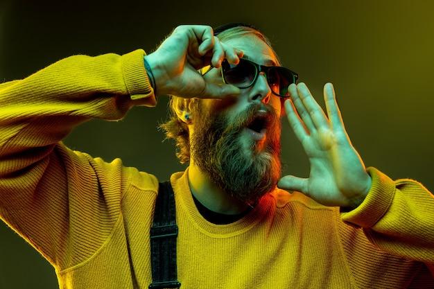 Porträt der kaukasischen frau auf gradientenstudiohintergrund im neonlicht. schönes männliches modell mit hipster-stil in gläsern. konzept der menschlichen emotionen, gesichtsausdruck, verkauf, anzeige. glücklich, anrufend.