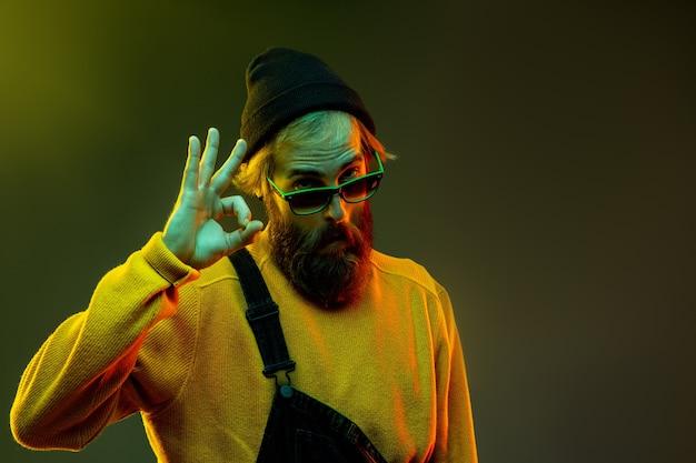 Porträt der kaukasischen frau auf gradientenstudiohintergrund im neonlicht. schönes männliches modell mit hipster-stil in gläsern. konzept der menschlichen emotionen, gesichtsausdruck, verkauf, anzeige. schön zeigen.