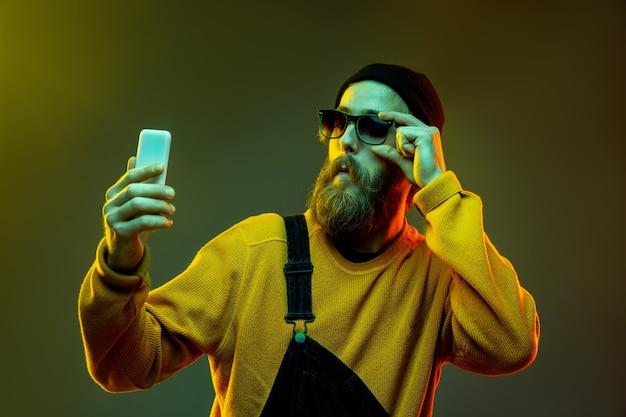 Porträt der kaukasischen frau auf gradientenstudiohintergrund im neonlicht. schönes männliches modell mit hipster-stil in gläsern. konzept der menschlichen emotionen, gesichtsausdruck, verkauf, anzeige. telefon benutzen.