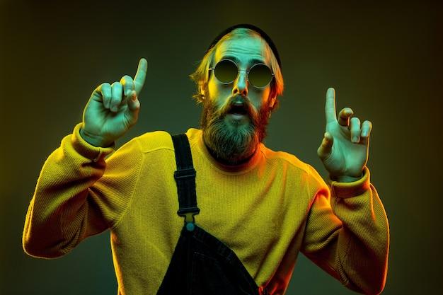 Porträt der kaukasischen frau auf gradientenstudiohintergrund im neonlicht. schönes männliches modell mit hipster-stil in gläsern. konzept der menschlichen emotionen, gesichtsausdruck, verkauf, anzeige. zeigen, wählen.