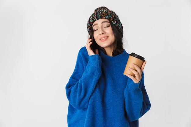 Porträt der kaukasischen frau, die wintermütze trägt, die auf handy spricht und kaffee zum mitnehmen trinkt, während sie steht, lokalisiert auf weiß