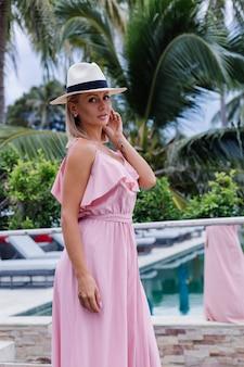 Porträt der kaukasischen frau im romantischen eleganten rosa langen kleid im urlaub im luxuriösen reichen villenhotel mit erstaunlicher tropischer palmenansicht-frau im klassischen weißen hut