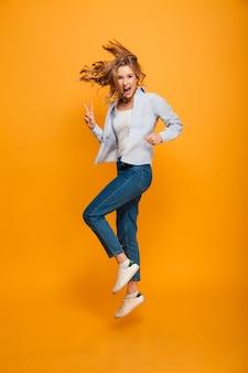 Porträt der kaukasischen frau in voller länge, die jeans und turnschuhe trägt, die mit friedensfingern springen oder laufen, lokalisiert über gelbem hintergrund