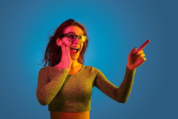 Porträt der kaukasischen frau lokalisiert auf blauem studiohintergrund im neonlicht