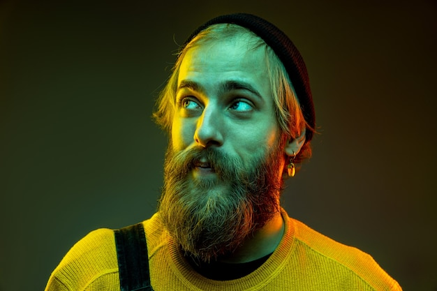 Porträt der kaukasischen frau lokalisiert auf gradientenstudiohintergrund im neonlicht. schönes männliches modell mit hipster-stil. konzept der menschlichen emotionen, gesichtsausdruck, verkauf, anzeige. seite betrachten.