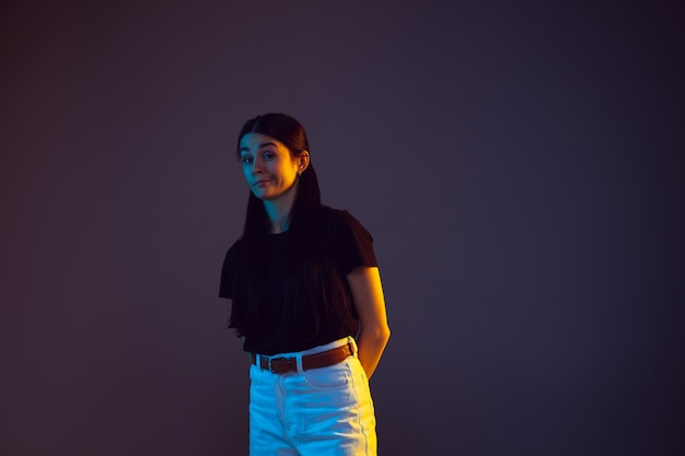 Porträt der kaukasischen jungen frau auf dunklem hintergrund