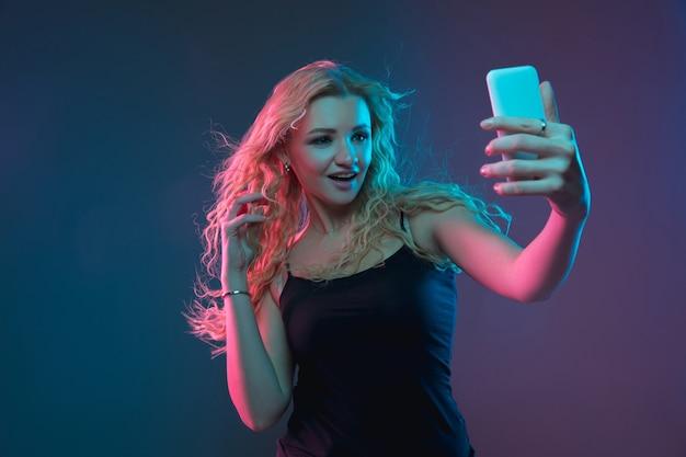 Porträt der kaukasischen jungen frau auf gradientenhintergrund im neonlicht. schönes weibliches modell mit ungewöhnlichem blick. konzept der menschlichen emotionen, gesichtsausdruck, verkauf, anzeige. selfie machen, wetten, einkaufen.