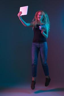 Porträt der kaukasischen jungen frau auf gradientenhintergrund im neonlicht. schönes weibliches modell mit ungewöhnlichem blick. konzept der menschlichen emotionen, gesichtsausdruck, verkauf, anzeige. springen, lächeln, sieht glücklich aus.