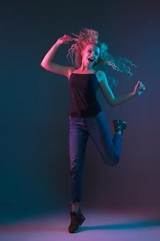 Porträt der kaukasischen jungen frau auf gradientenhintergrund im neonlicht. schönes weibliches modell mit ungewöhnlichem blick. konzept der menschlichen emotionen, gesichtsausdruck, verkauf, anzeige. springen, lächelnd.