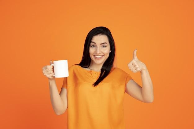 Porträt der kaukasischen jungen frau auf orange studiohintergrund. schönes weibliches brünettes modell im hemd. konzept der menschlichen emotionen, gesichtsausdruck, verkauf, anzeige. copyspace. kaffee oder tee trinken.