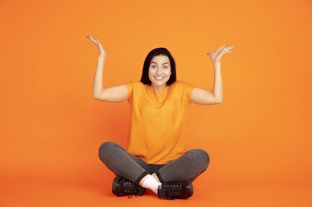 Porträt der kaukasischen jungen frau auf orange studiohintergrund. schönes weibliches brünettes modell im hemd. konzept der menschlichen emotionen, gesichtsausdruck, verkauf, anzeige. copyspace. nach oben zeigend.