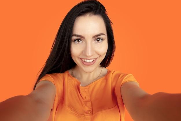 Porträt der kaukasischen jungen frau auf orange studiohintergrund. schönes weibliches brünettes modell im hemd. konzept der menschlichen emotionen, gesichtsausdruck, verkauf, anzeige. copyspace. selfie machen und lächeln.