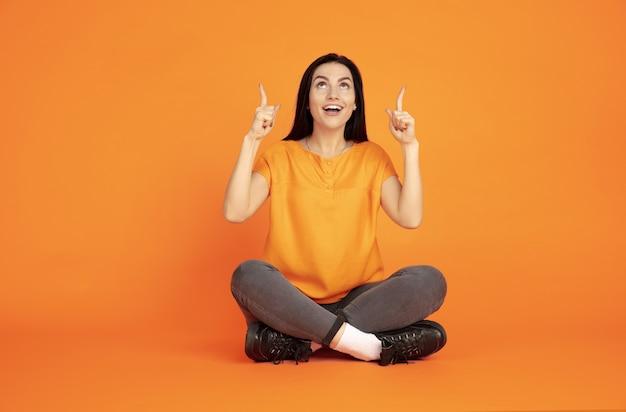Porträt der kaukasischen jungen frau auf orange