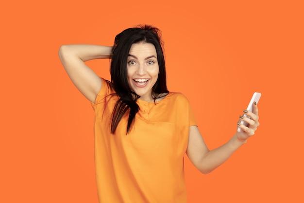 Porträt der kaukasischen jungen frau auf orangeem studiahintergrund. schönes weibliches brünettes modell im hemd. konzept der menschlichen emotionen, gesichtsausdruck, verkauf, anzeige. copyspace. selfie machen, wette gewinnen.