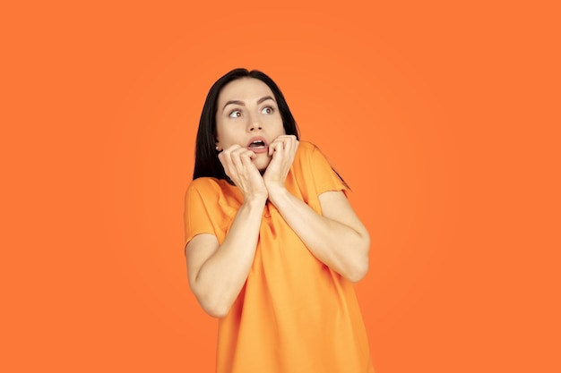 Porträt der kaukasischen jungen frau auf orangeem studiahintergrund. schönes weibliches brünettes modell im hemd. konzept der menschlichen emotionen, gesichtsausdruck, verkauf, anzeige. copyspace. sieht ängstlich aus.