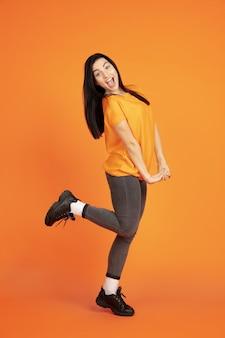 Porträt der kaukasischen jungen frau auf orangeem studiahintergrund. schönes weibliches brünettes modell im hemd. konzept der menschlichen emotionen, gesichtsausdruck, verkauf, anzeige. copyspace. tanzen, lachen.