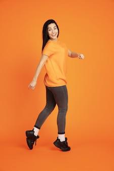 Porträt der kaukasischen jungen frau auf orangeem studiahintergrund.