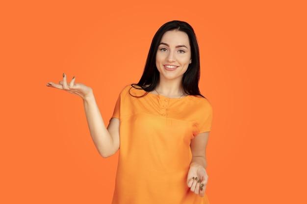 Porträt der kaukasischen jungen frau auf orangefarbenem hintergrund